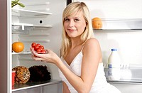 Woman taking out a box of tomatoes from the fridge