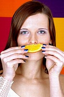 Woman covering her mouth with a cut orange