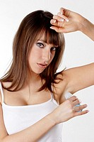 Woman applying deodorant on her underarm