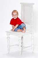 Boy sitting on a big wooden chair