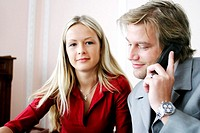 Businessman talking on the mobile phone with his secretary sitting by the side (thumbnail)