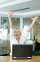 Businesswoman rejoicing after reading the good news in her e-mail