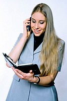 Businesswoman referring to her organizer while talking on the mobile phone