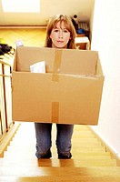 Woman carrying a box up the stairs