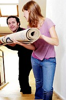 Couple carrying a rolled up carpet to the second floor