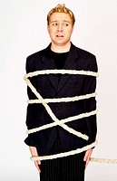 Businessman being tied up with rope