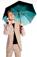 Businessman holding an umbrella while talking on the mobile phone