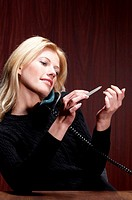 Businesswoman shaping her fingernails while talking on the phone (thumbnail)