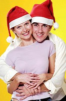 Loving couple wearing christmas hats
