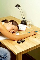 Woman sleeping while doing her assignment