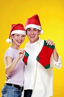 Couple in christmas hats holding christmas socks