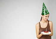 Girl with party hat holding a birthday cake
