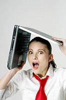 Shocked woman shielding her face with a laptop (thumbnail)