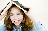 Woman covering her head with a book