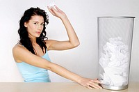 Woman about to throw a crumpled paper into the dustbin