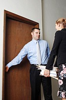 Businessman helping his colleague to open the door (thumbnail)
