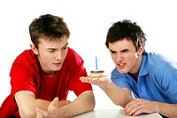 Men looking at a small birthday cake