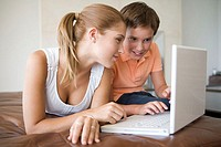 Brother and sister using laptop (thumbnail)