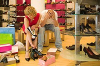 Man despairing as woman chooses shoes