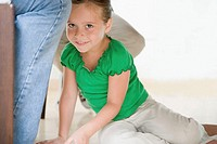 Girl sitting by adult legs
