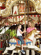 Mother and daughter on carousel