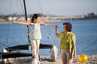 Grandmother helping girl walk on catamaran