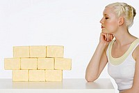 Young woman sat next to blocks of butter