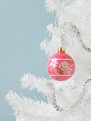 Pink ornament on a white Christmas tree