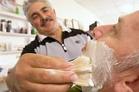 Hairdresser applying shaving cream on man´s face