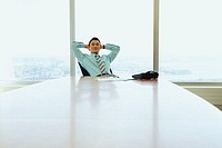Businessman leaning back in his chair (thumbnail)
