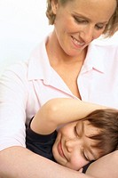 Little boy lying on the lap of a mature woman, close-up