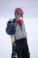 Boy (8-9) in ski wear and goggles posing on ski slope, portrait