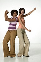 Two friends dancing back to back, posing in studio, portrait