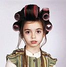 Girl (7-9) with hair in curlers, portrait