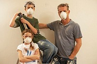 Father with son and daughter (7-9) wearing masks and goggles, portrait