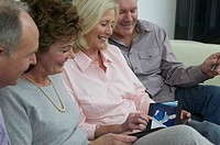 Two mature couples on sofa looking at photo album, smiling, close-up
