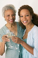 Mother and daughter toasting champayne glasses, smiling, portrait