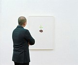 Man in art gallery facing picture, rear view