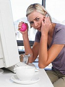 Businesswoman using PC and mobile phone at desk holding stressball