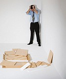 Businessman pulling hair, standing by flat-pack