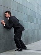 Businessman listening at wall, bending at knees, side view
