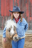 Girl (7-9) standing in front of barn with Shetland pony, portrait