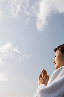 Young woman praying outdoors, low angle view