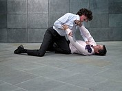Two businessmen fighting, younger man grabbing colleague´s tie