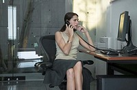 Woman using telephone at desk with computer