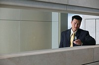 Businessman in hallway with mobile phone
