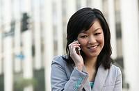 Woman using mobile phone, smiling