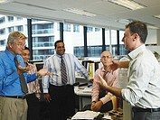 Group of male colleagues talking in office