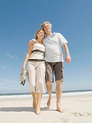 Mature couple embracing on beach, smiling, low angle view