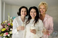 Three women holding glasses of champagne, smiling, portrait